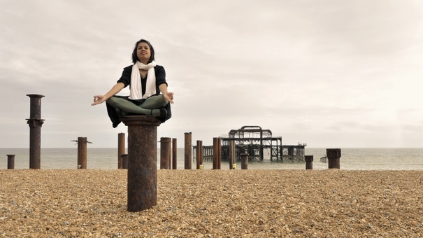 Young Asian woman meditating next to the West Pier in Brighton, England, UK